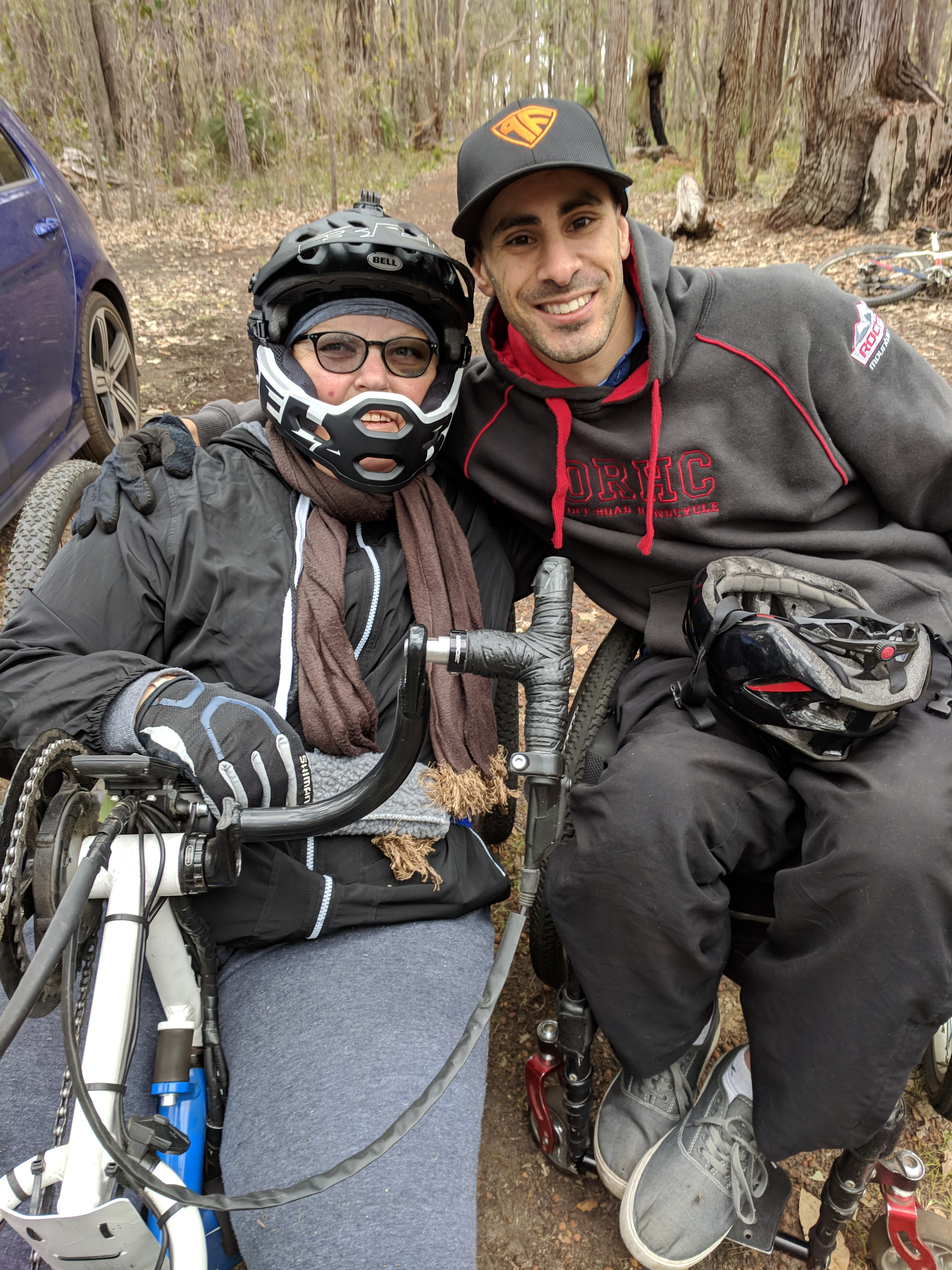 photo of female handcyclist in full helmet and male wheelchair user embracing each other with big smiles